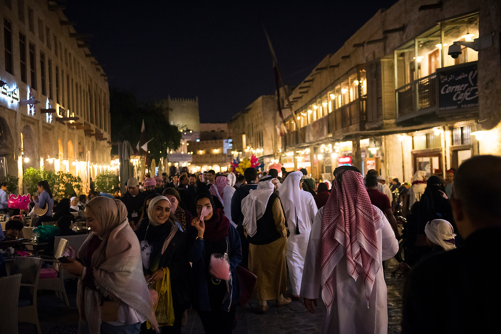 Nightlife at the popular pedestrian area of Souk Waqif in Doha, Qatar. Two ladies in the foreground are carrying cotton candy.