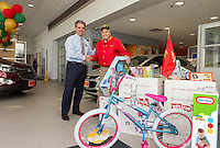 """Tom Cantin greets Bob Pelland on Tuesday morning  """"pick up"""" day for the US Marine Corps Toys for Tots donated at Cantin's Chevrolet.    (Karen Bobotas/for the Laconia Daily Sun)"""