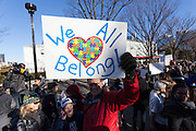 A man holds a sign saying We All belong at a protest march and rally organised by the Alliance for an Inclusive America group against the perceived anti-Muslim and anti-foreigner immigration policies of President Donald Trump, Shibuya, Tokyo, Japan. Sunday February 12th 2017. The Alliance of an Inclusive America is a multi-faith non-partisan group. About 250 Americans, other ex-pats and japanese people took part in the march to show people around the world they reject the Executive Order President Trump enacted at the end of January, indefinitely suspending the resettlement of Syrian refugees and temporarily banning people from seven majority Muslim countries from entering the United States.