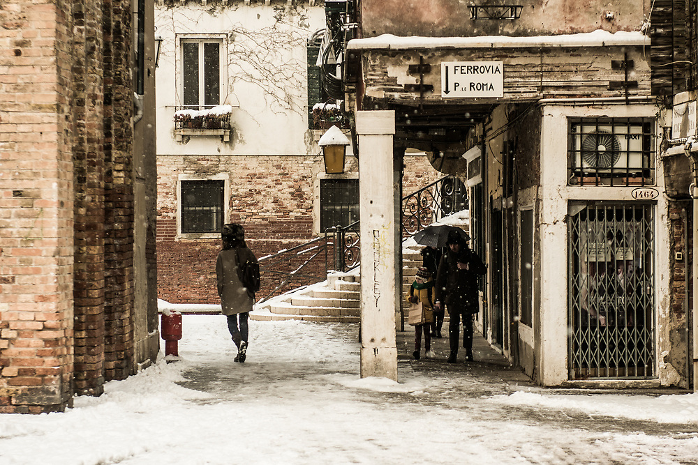 """VENICE, ITALY - 28th FEBRUARY/01st MARCH 2018<br /> People walk under a portico to protect themselves by the snowfall in Venice, Italy. A blast of freezing weather called the """"Beast from the East"""" has gripped most of Europe in the middle of winter of 2018, and in Venice A snowfall has covered the city with white, making it fascinating and poetic for citizen and tourists.   © Simone Padovani / Awakening"""