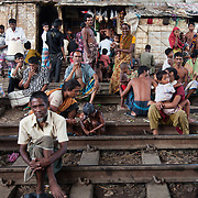 Life in the slums by the  railway tracks in Tejgaon. Homes are build closely to the tracks leading in and out of one of Dhaka's main train stations and life is goes on as in any othr part of Dhaka in spite of the dangerous proximity to the live tracks and trains passing at regular intervals.People sheltering from the rain under the over pass.