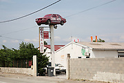 BMW car raised high above a Casse Auto repair shop in Carcassonne, Languedoc-Roussillon, France.