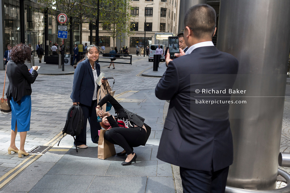 An Asian business lady visitor comically contorts her body in order to take a photo of a colleague against London skyscrapers in the City of London, (aka The Square Mile) the capital's financial district, on 2nd September 2019, in London, England.