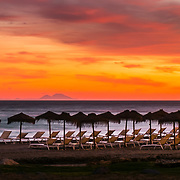 Deserted deck chairs assist to a spectular sunst over Marbella coast. In the horizon, the african coast and Rock of Gibraltar.