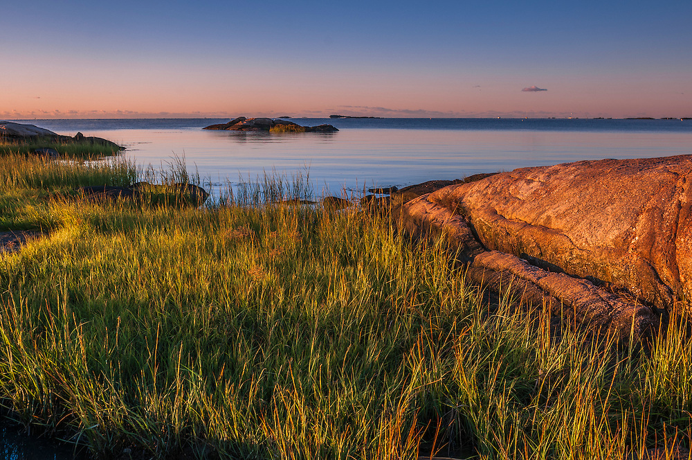 Strong first light on grasses, rocks, and boulders in water, Chaffinch Island Park, Guilford, CT