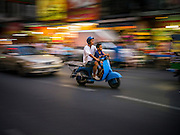 29 DECEMBER 2012 - BANGKOK, THAILAND: People on a motorscooter on Yaowarat Road in Samphanthawong district in the Chinatown area of Bangkok, Thailand.       PHOTO BY JACK KURTZ