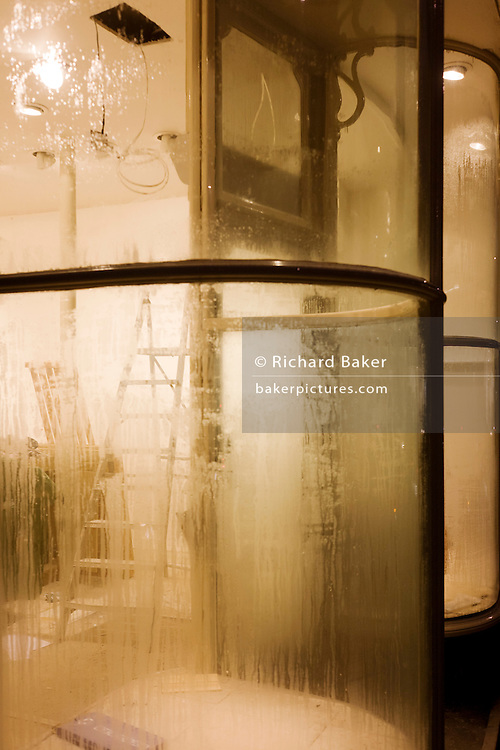 Steamy window of a refurbished shop in Chelsea, with workmens' ladders and building equipment.