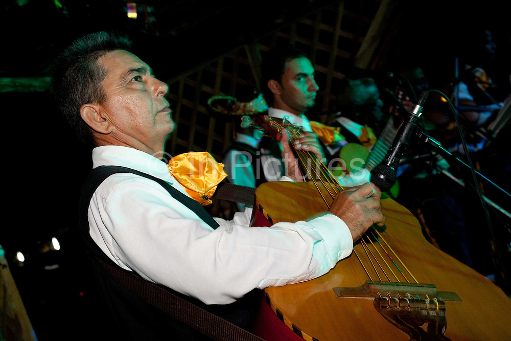 Cuban musicians performing music on stage, singing, trumpets violins, wearing country style suits attire waistcoats and sombrero hats. Cuban locals attend a Rodeo in Ciego de Avila province, Cuba.