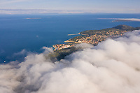 Aerial view above the clouds of Veli Lošinj cityscape, Croatia.