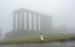 Edinburgh, Scotland, UK. 13 June 2020. A thick fog ,or haar as it is called locally, covers the city and obscures the famous tourist viewpoint from Calton Hill. Normally the viewpoint is busy with tourists , however, with the fog and Covid-19 lockdown continuing, only a few members of the public ventured up the hill today. A dog walker and the National Monument shrouded in haar. Iain Masterton/Alamy Live News