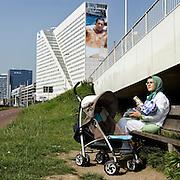 Nederland Rotterdam 7 juni 2007 20070607.Moslim vrouw voedt baby met de fles op een bankje aan de maasboulevard, op de achtergrond een reusachtig grote reclame op billboard gebouw Ernst & Young aan de Boompjes met halfnaakte man van Dolce Gabbana..Reclametechnieken: Bekend is de formule AIDA: attention, interest, desire, action: de aandacht opwekken, de interesse wekken, het verlangen opwekken, tot actie overhalen.Mental Preference: Techniek om mensen op een of meerdere van hun mentale denkstijlen aan te spreken: logisch; pragmatisch; emotioneel of creatief.Associatie: Reclamemakers proberen hun product te associâren met aangename of begeerlijke dingen om hun eigen product even begerig te maken. Hiervoor gebruiken ze modellen, landschappen en ander vergelijkbaar beeldmateriaal.Aspirationele leeftijd: Door de boodschap te richten op de aspirationele leeftijd van de doelgroep, wordt deze voor de daadwerkelijke doelgroep aantrekkelijker..Foto David Rozing