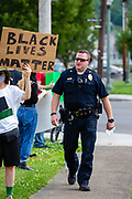 Shamokin Police Chief Darwin Tobias III walks by protesters at Market and Independence Streets in Shamokin, PA where about 30 people gathered to protest police violence and racism.