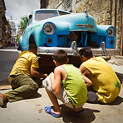 Man man repairs a broken down car in the street while another man and a boy look on in Havana, Cuba.