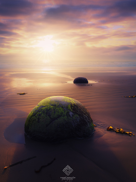 In my trip to the eastern coast of South Island of New Zealand in 2015, I had to pass on Moeraki Boulders to photograph, The morning was very cold, and the clouds covered the horizon and obscured the sun.<br /> The condition frustrated me somewhat, but I did not lose hope and waited for the right moment.<br /> Finally, the sun comes out through the clouds and I got my prise. I hope I have succeeded in capturing this moment.
