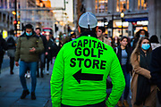 Human signboard for a golf store standing in a crowded Oxford Circus in London on the last day of shopping before the second national coronavirus lockdown on 4th November 2020 in London, United Kingdom. Oxford Street's infamous 'Golf Sale' man, an emblem in the eyes of many of everything that is wrong with London's premier shopping thoroughfare, was banned in 2008. The 'golf store jacket' was a workaround. Radical measures will be needed to persuade shoppers to return in large numbers after December 2 when lockdown ends. The new national lockdown is a huge blow to the economy and for individuals who were already struggling, as Covid-19 restrictions are put in place until 2nd December across England, with all non-essential businesses closed.