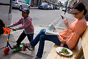 Cafe society in the popular Broadway Market, a gentrified area of the otherwise poor borough of Hackney and Haggerston. A young woman sits on an outside café bench to enjoy summer weekend sunshine, a toast snack and a text to friends on her smartphone. Passing her is a young boy on his scooter, one foot on the board and the other propelling him along the street.