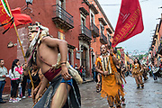 Aztec indians dance in a procession through the historic city during the week long fiesta of the patron saint Saint Michael September 24, 2017 in San Miguel de Allende, Mexico.