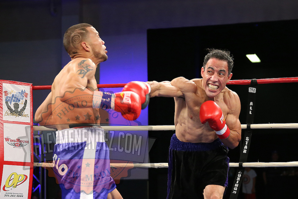 """Juan Castillo (purple shorts) fights against Luis Rodriguez during a """"Boxeo Telemundo"""" boxing match at the Kissimmee Civic Center on Friday, July 18, 2014 in Kissimmee, Florida. Castillo won the bout.  (AP Photo/Alex Menendez)"""