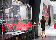 Manhattan, New York, USA. April 12, 2017.  Reflection of red Audi Sport car is seen on glass panel, as woman walks past at the New York International Auto Show, NYIAS, at the Javits Center.