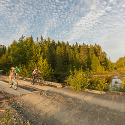 A woman and her kids ride bikes near Pushineer Pond in Aroostook County, Maine. Deboullie Public Reserve Land.