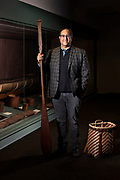 Darren Ranco, PhD, anthropologist, photographed at the Hudson Museum, Orono. Dr. Ranco holds a Penobscot canoe paddle (ca.1900) and stands before a birch bark canoe (ca.1888). The modern pack basket is by Gabriel Frey. Together, the paddle, basket and canoe represent the essential travel gear of his ancestors. Dr. Ranco is a citizen/member of the Penobscot Nation, Associate Professor of Anthropology, Chair of Native American Programs and Coordinator of Native American Research at the University of Maine, and a team leader of the Sustainability Solutions Initiative's Emerald Ash Borer project. His research focuses on environmental justice, particularly the ways in which indigenous communities resist environmental destruction and protect cultural resources.