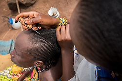 3 June 2019, Djohong, Cameroon: 15-year-old Adija (right) braids her mother Didi's (left) hair by their home in the Borgop refugee camp. Adija says she has been braiding hair since she was 13 years old, and today knows more than ten different types of braids. The end of Ramadan is drawing near, so people in the mostly Muslim Borgop refugee camp are decorating themselves in preparation for celebrations of the end of the annual period of fasting. The Borgop refugee camp is located in the municipality of Djohong, in the Mbere subdivision of the Adamaoua regional state in Cameroon. Supported by the Lutheran World Federation since 2015, the camp currently holds 12,300 refugees from the Central African Republic.