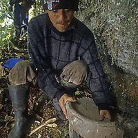 Amazonian homesteader Hernan Borges examines grinding stone in pre-Incan city lost in Peruvian cloud forest.