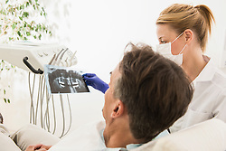 Female dentist discussing an X-ray report with patient, Munich, Bavaria, Germany