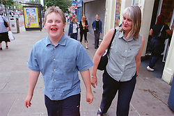 Mother walking along street with teenage son with Downs Syndrome,