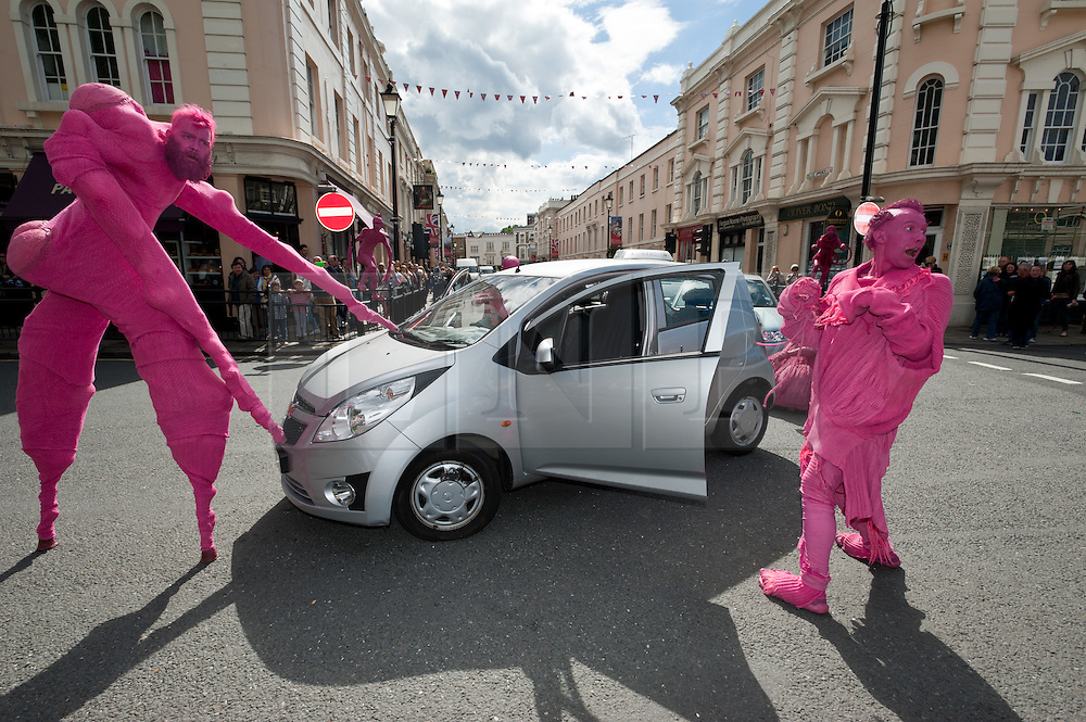 """© Licensed to London News Pictures. 24/06/2012. London, UK.  Aliens land in Greenwich and stop traffic.  """"The Invasion"""" is a Slovenian street theatre act comprising of pink aliens which roam around Greenwich as part of Greenwich Fair.  Greenwich Fair is a part of the Greenwich & Docklands International Festival, taking place between 21-30 June.  Photo credit : Richard Isaac/LNP"""