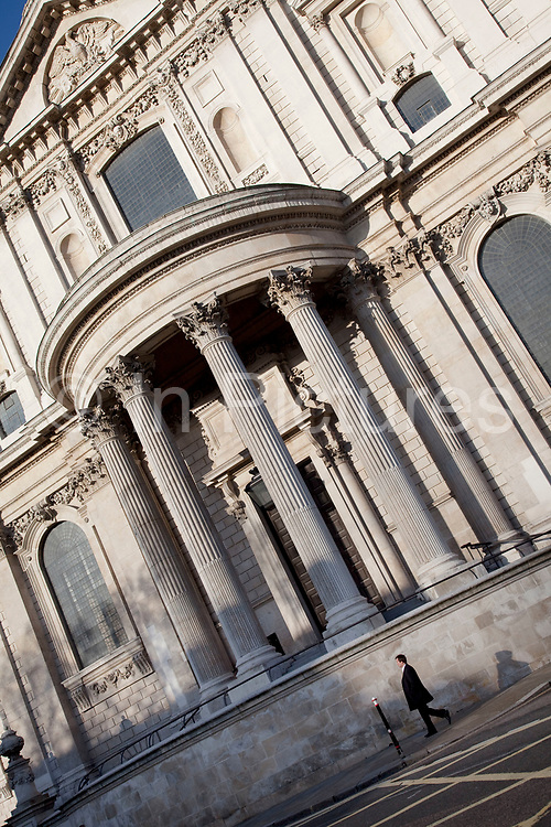 Man walking past St Paul's Cathedral is dwarfed by the sheer scale of the building. London