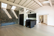Empty living room with dark kitchen and island, wooden beams