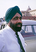 Head and shoulders portrait of bearded Sikh man wearing tie and green turban, New Delhi, India 1964