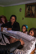 Together with young relatives the widow of a deceased Roma man grieve beside his open coffin during the wake held in their home in Valea Seaca Villlage in Bacau County, Romania.