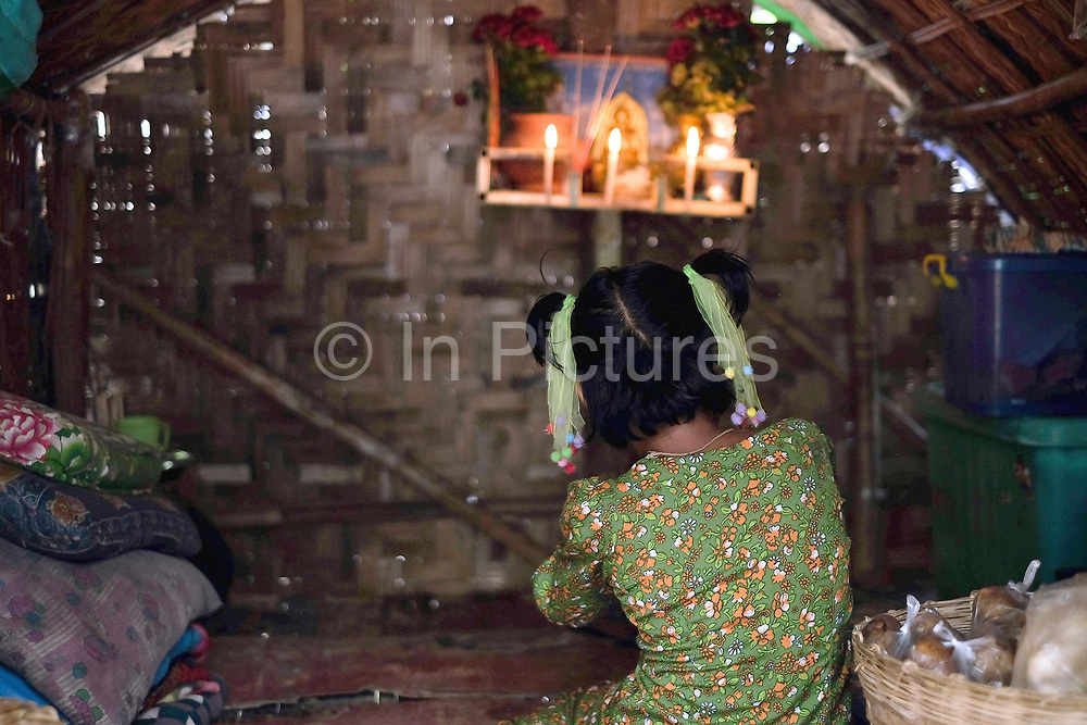 Portrait of a young girl living praying in front of a Buddhist shrine by the Ayeyarwady river on 25th May 2016 in Mandalay, Myanmar. Thanaka is worn by many Burmese women and girls as a traditional sunscreen and moisturiser