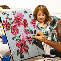 Guido Lozada from Honolulu, Hawaii finishes his painting August 23, 2018 at the Art123 Gallery in Downtown Gallup, New Mexico during the Gallup ARTS Wine and Paint event.