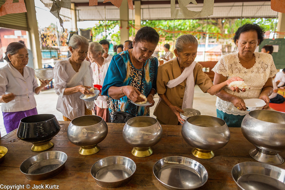 24 MAY 2013 - MAE SOT, THAILAND:    Women make merit by donating food to the monks at Wat Mae Pa in Mae Sot on Visakha Puja Day. Visakha Puja (Vesak) marks three important events in the Buddha's life: his birth, his attainment of enlightenment and his death. It is celebrated on the full moon of the sixth lunar month, usually in May on the Gregorian calendar. This year it is on May 24 in Thailand and Myanmar. It is celebrated throughout the Buddhist world and is considered one of the holiest Buddhist holidays.    PHOTO BY JACK KURTZ