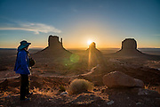 The photographer admires West & East Mittens and Merrick Butte at sunrise in Monument Valley Navajo Tribal Park, Arizona, USA. The Western movie director John Ford set several popular films here.