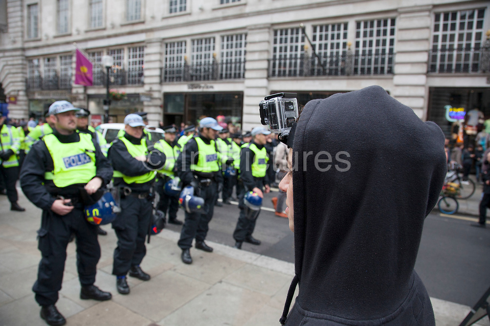 London, UK. Tuesday 11th June 2013. Protester with a CCTV camera strapped to her head to film police during demonstration against the upcoming G8 summit in central London, UK.