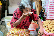 A vegetable vendor drinks tea from a saucer at an early morning street market in Yangon, Myanmar on 18th May 2016.  A large variety of local products are available for sale in fresh markets all over Yangon, all being sold on small individual stalls