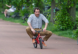 © Licensed to London News Pictures 11/06/2021. Greenwich, UK. A dad rides off on his young son's bike and looks to be loving it. A warm cloudy humid day in London as people enjoy some time in Greenwich park. Temperatures across the UK are forecast to be hotter than Portugal at the weekend with Monday set to be the hottest. Photo credit:Grant Falvey/LNP