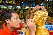 "12 NOVEMBER 2012 - BANGKOK, THAILAND:   A shop worker puts the eyes on a Buddha statue in front of a shop on Bamrung Muang Street in Bangkok. The eyes are cut from pieces of plastic and glued to the statue. Thanon Bamrung Muang (Thanon is Thai for Road or Street) is Bangkok's ""Street of Many Buddhas."" Like many ancient cities, Bangkok was once a city of artisan's neighborhoods and Bamrung Muang Road, near Bangkok's present day city hall, was once the street where all the country's Buddha statues were made. Now they made in factories on the edge of Bangkok, but Bamrung Muang Road is still where the statues are sold. Once an elephant trail, it was one of the first streets paved in Bangkok. It is the largest center of Buddhist supplies in Thailand. Not just statues but also monk's robes, candles, alms bowls, and pre-configured alms baskets are for sale along both sides of the street.    PHOTO BY JACK KURTZ"