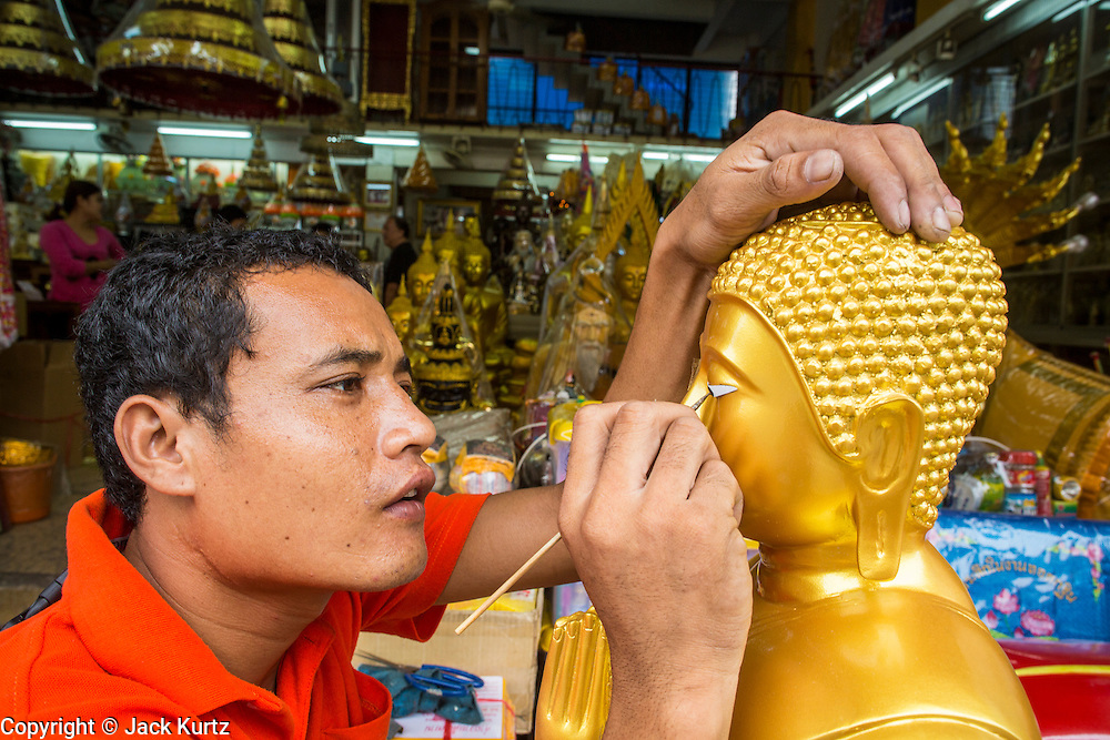 """12 NOVEMBER 2012 - BANGKOK, THAILAND:   A shop worker puts the eyes on a Buddha statue in front of a shop on Bamrung Muang Street in Bangkok. The eyes are cut from pieces of plastic and glued to the statue. Thanon Bamrung Muang (Thanon is Thai for Road or Street) is Bangkok's """"Street of Many Buddhas."""" Like many ancient cities, Bangkok was once a city of artisan's neighborhoods and Bamrung Muang Road, near Bangkok's present day city hall, was once the street where all the country's Buddha statues were made. Now they made in factories on the edge of Bangkok, but Bamrung Muang Road is still where the statues are sold. Once an elephant trail, it was one of the first streets paved in Bangkok. It is the largest center of Buddhist supplies in Thailand. Not just statues but also monk's robes, candles, alms bowls, and pre-configured alms baskets are for sale along both sides of the street.    PHOTO BY JACK KURTZ"""