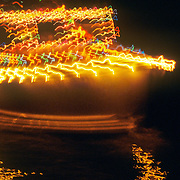 A moving lobster boat decorated with Christmas lights at night. Boothbay Harbor, Maine
