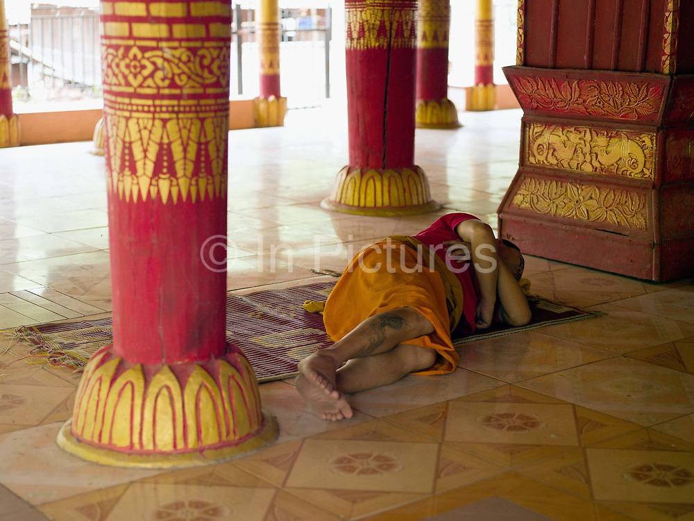 A Buddhist monk asleep on the temple floor in the Tai Lue village of Ban Ngay Neua, Phongsaly province, Lao PDR