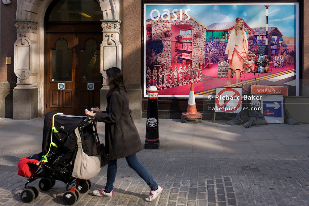 Mother pushes child's buggy and roadworks signs below an Oasis fashion poster featuring a young woman in a utopian fantasy about to cross a road with a trolley.