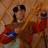 A young Mongolian musician tunes a traditional fiddle in his home in Ulaanbaatar, which he and his father have decorated to look like a ger (yurt).
