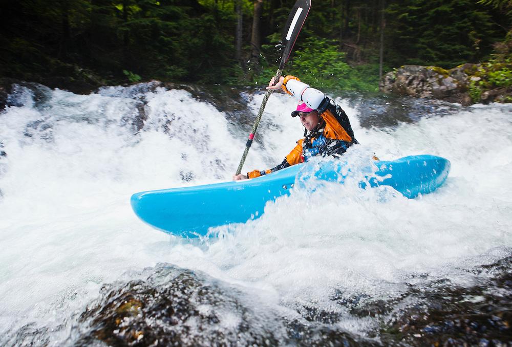 A woman kayaking down a series of small waterfalls, Snoqualmie River, Washington, USA.
