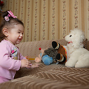 """CAPTION: Stella squeals with delight as she comes face to face with one of her soft toys. """"I don't think Stella yet understands that she's different to other children"""", her mother observes. """"But if she were to continue with this defect, it would be difficult for her to live that way"""". LOCATION: Volgograd, Russia. INDIVIDUAL(S) PHOTOGRAPHED: Stella Aharonyan."""