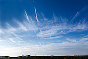 airplane vapour trails converging In a blue sky with clouds